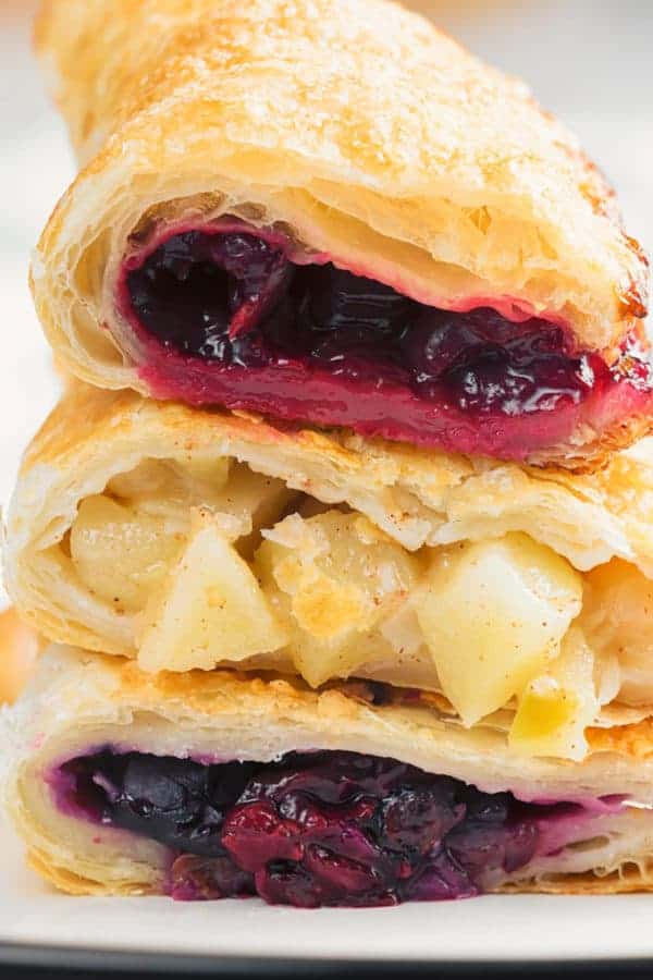 Hand Pies Stacked on top of each other, filled with apple and blueberry filling