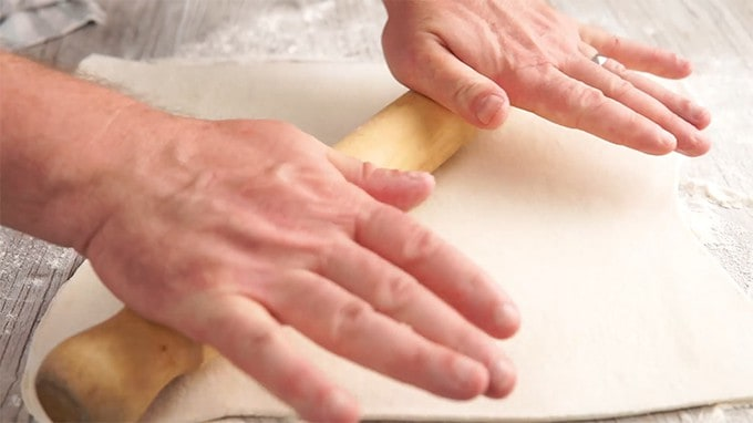 Person rolling dough with a rolling pin.