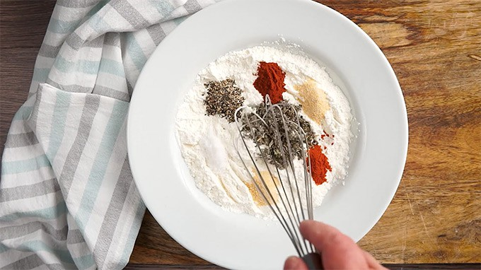 Seasonings and flour in a white bowl with a whisk and a tea towel on the side