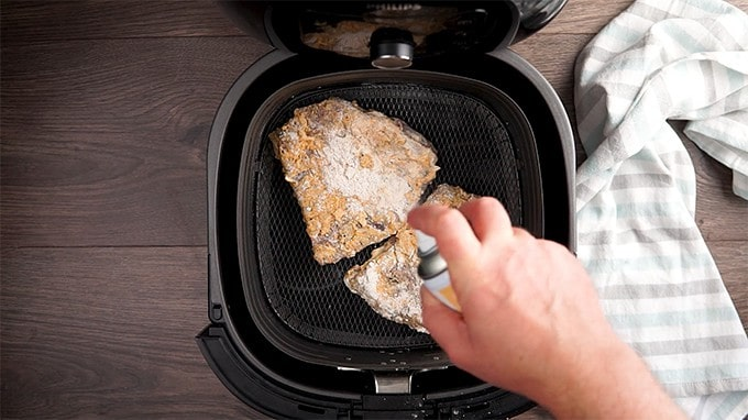 Breaded cube steaks being placed in the air fryer and sprayed with cooking spray.