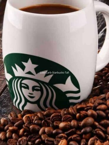 A white Starbucks mug sitting on a pile of coffee beans
