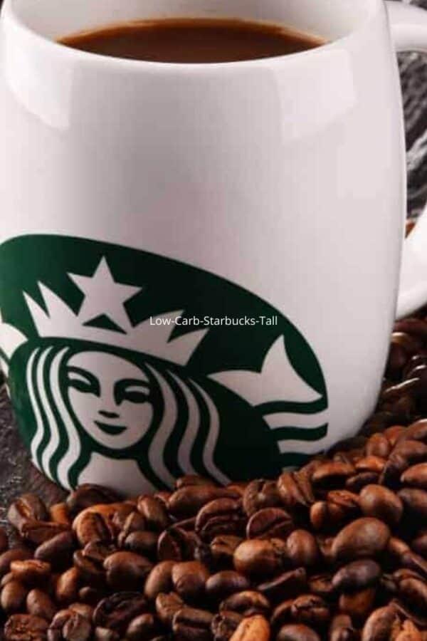 A white Starbucks mug sitting on a pile of coffee beans