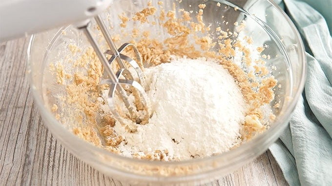 Flour Mixed into Butter and Sugar Mixture in a glass bowl with a mixer attachment