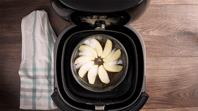 Sugar sprinkled on top of apples in a single layer in an air fryer.