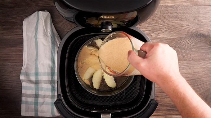 Pouring Batter on top of apples in an air fryer in a single layer.