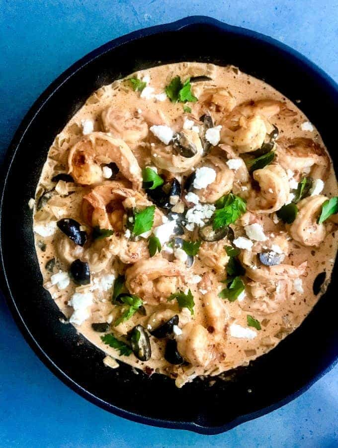 overhead shot of mediterranean shrimp with feta and olives in a black cast iron skillet