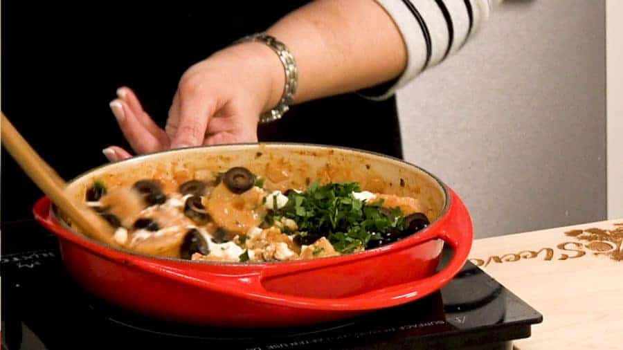Side shot of mixing shrimp, feta cheese and olives into the mixture in the sauce pan.