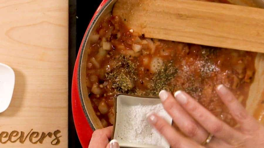 Overhead shot of adding salt to the other ingredients in the sauce pan.