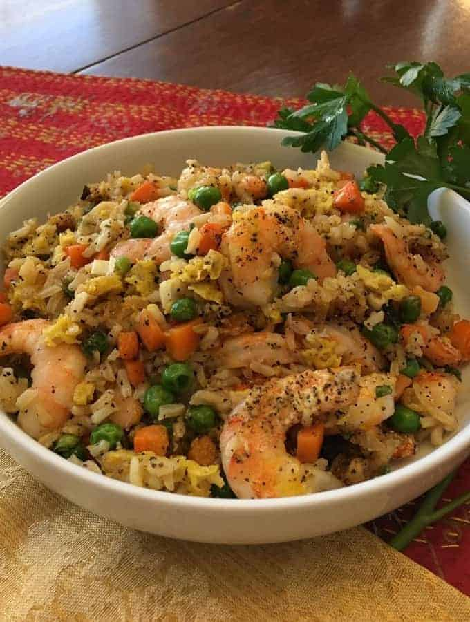 Air Fryer Shrimp with peas and carrots in a white bowl.