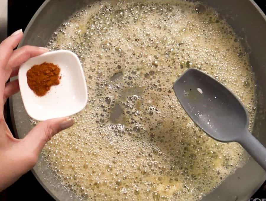 Overhead shot of adding seasonings to melted butter in a hot pan.
