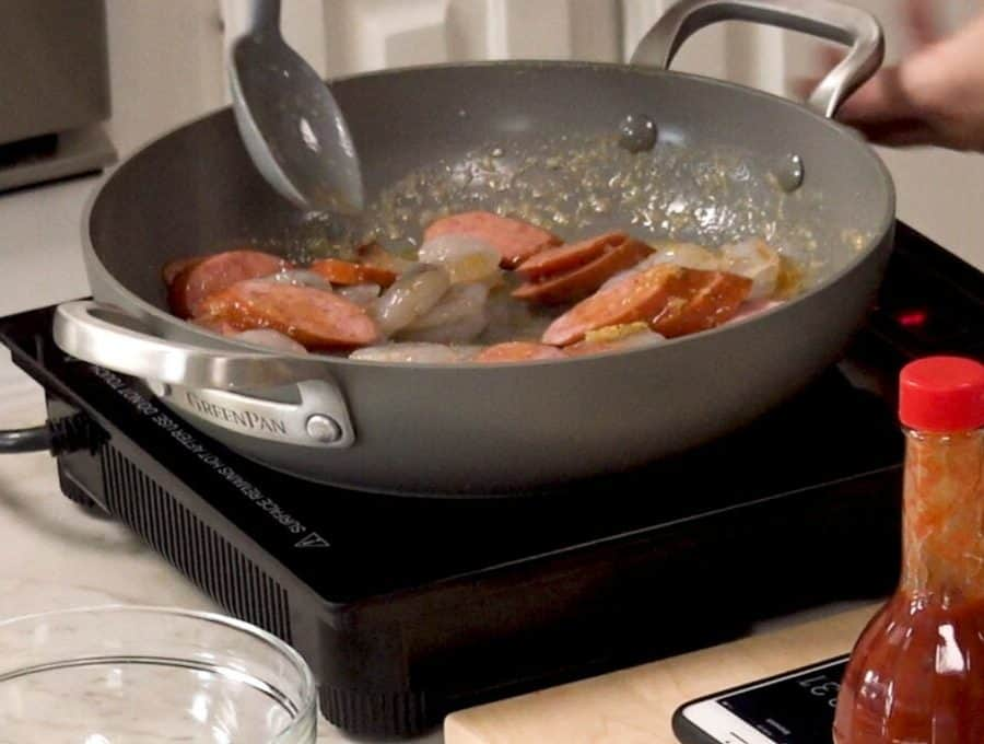 Side shot of cooking shrimp and sausage in a pan.