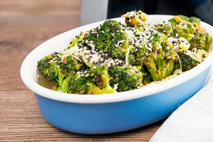 Sesame Ginger Broccoli Topped with white and black sesame seeds in a blue serving dish.