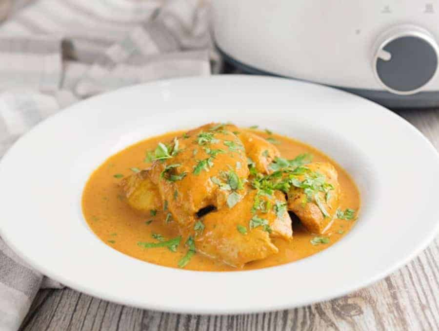 Side shot of slow cooker butter chicken in white dish.