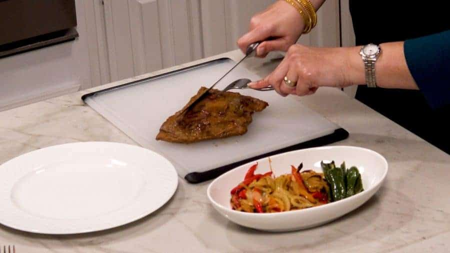 Side shot of cutting the flank steak with finished vegetables to the side in a separate plate.