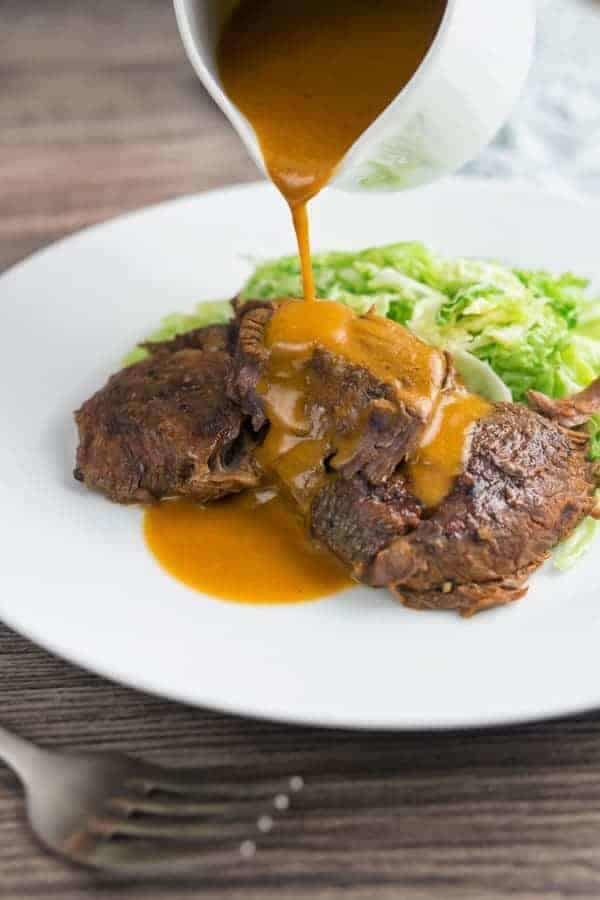 Instant Pot Braised brisket with sauce pouring on it