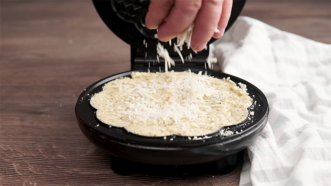 Side shot of Parmesan cheese being sprinkled on top of the chaffle mixture in the waffle maker.