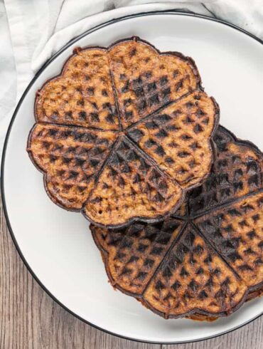 Two chocolate chaffles on a white plate overhead