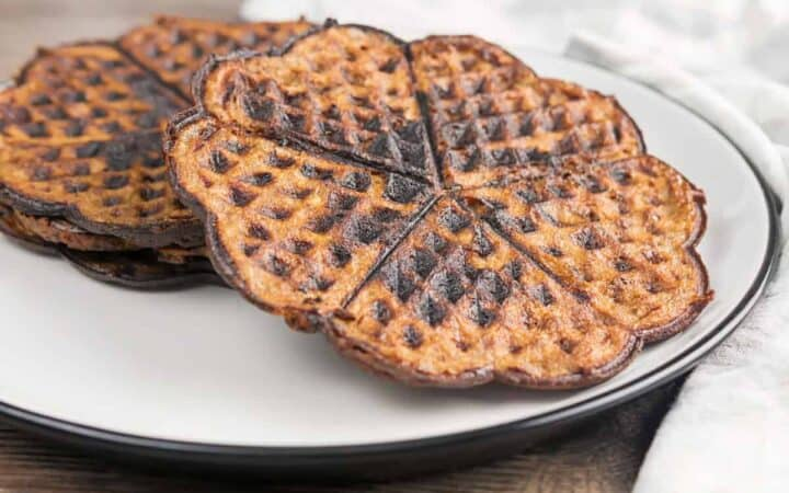 Two chocolate chaffles on a white plate sideways