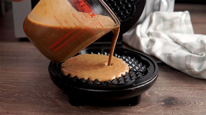Side shot of the batter being poured into the waffle maker.