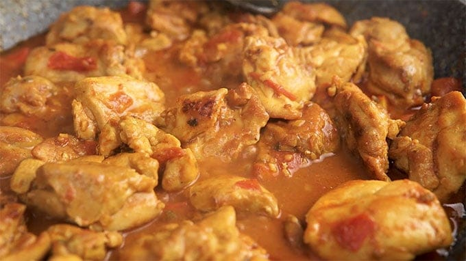 Side shot of Chicken Karahi cooking in a pan.
