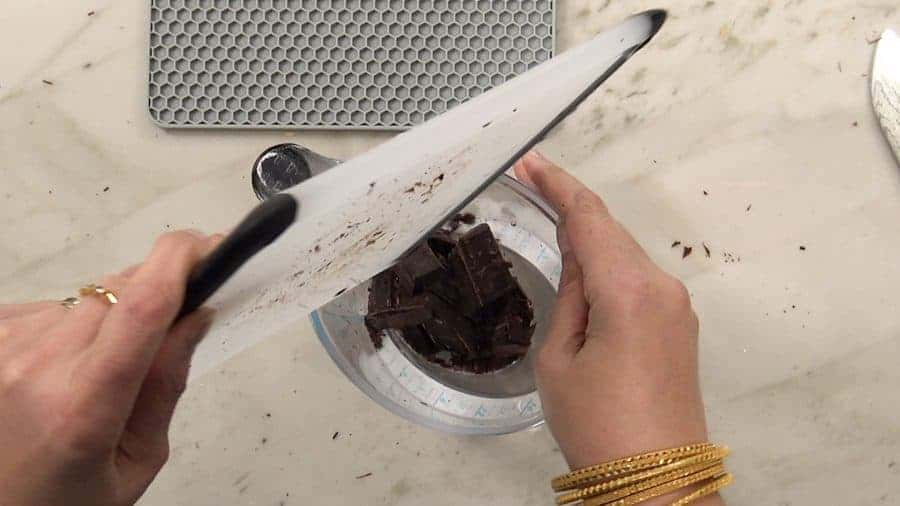 Overhead shot of adding the rough chopped chocolate to a microwave save container.