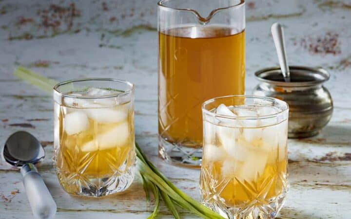 Pitcher of lemongrass tea with two glasses with ice and tea in them in the front