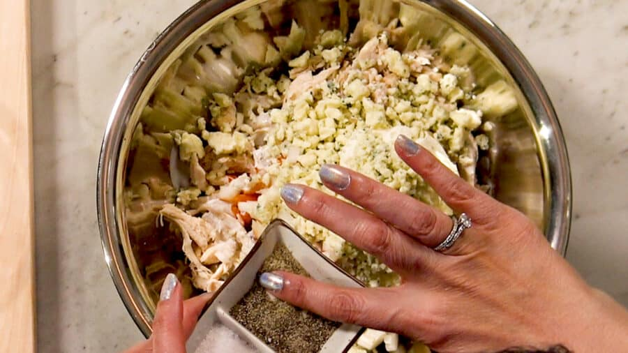 Overhead shot of adding pepper to the rest of the Buffalo Chicken Casserole ingredients in a mixing bowl.