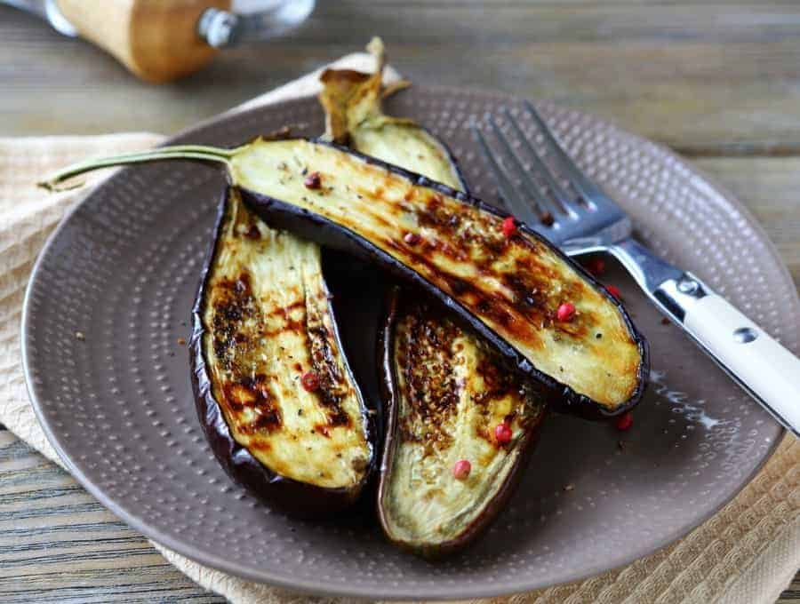 A plate of Roasted Eggplant with a fork and knife.