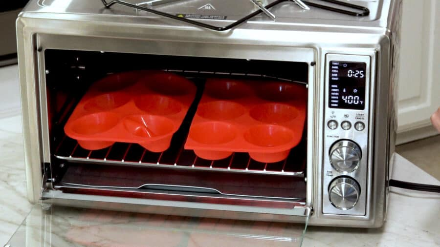side shot of a 12 muffin silicone pan in the oven.