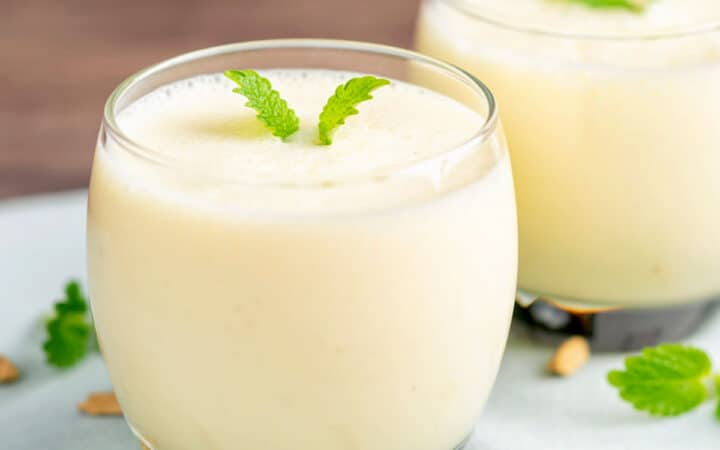 two glasses with mango lassi and garnish