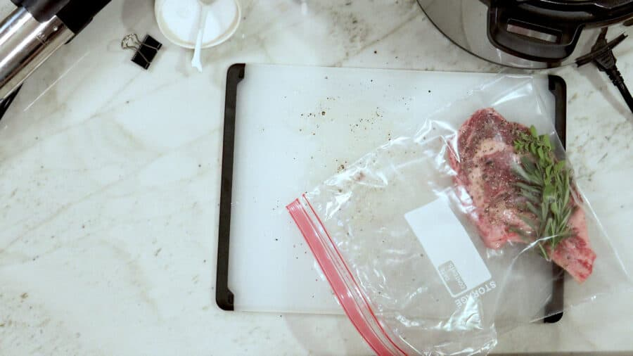 Overhead shot of the seasoned steak in a resealable plastic bag.