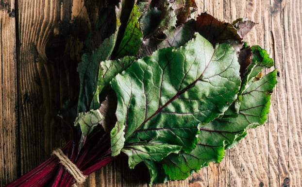 How to cook beets greens leaves against wood background