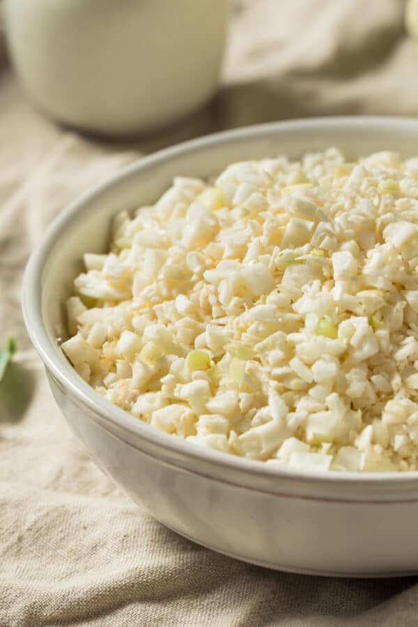 Close up of cauliflower rice in a white bowl ready to be cooked