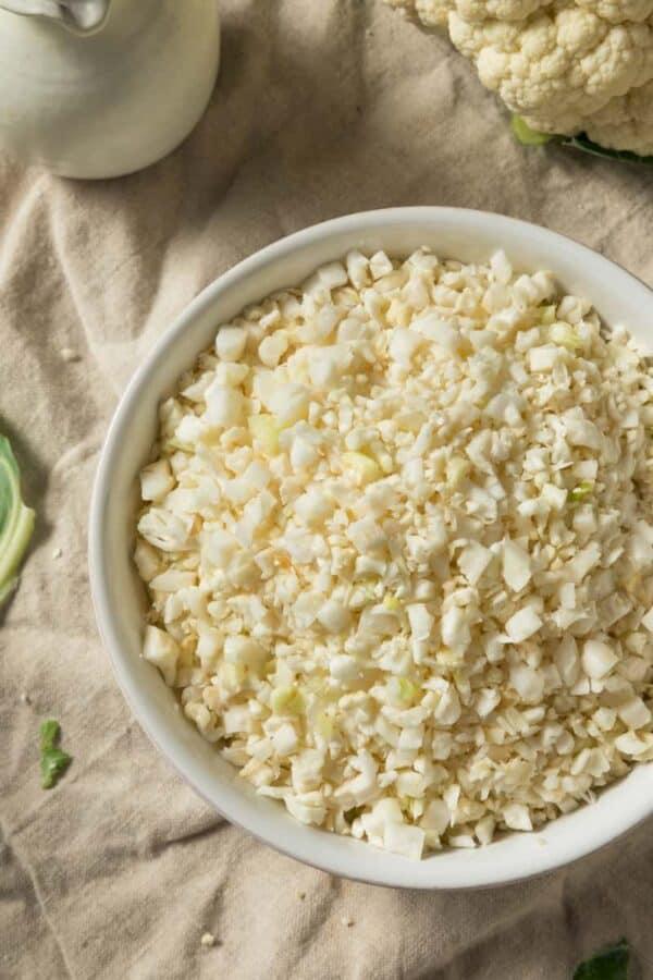 Raw cauliflower rice in a white bowl