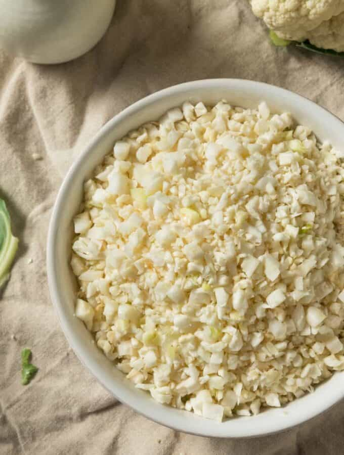 Raw cauliflower rice in a white bowl