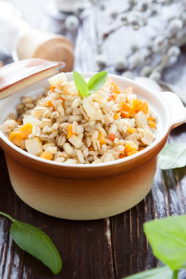 Cooked barley with carrots in an orange crock