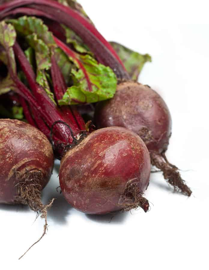 how to cook Beets with stems and greens on white background