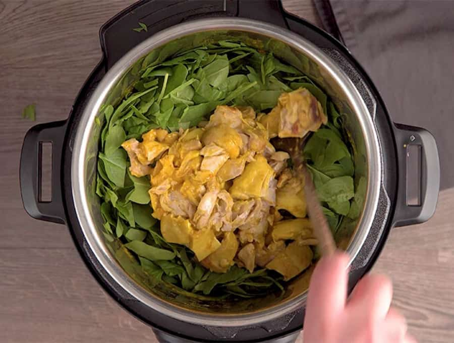 saucy chicken on a bed of spinach in an Instant Pot