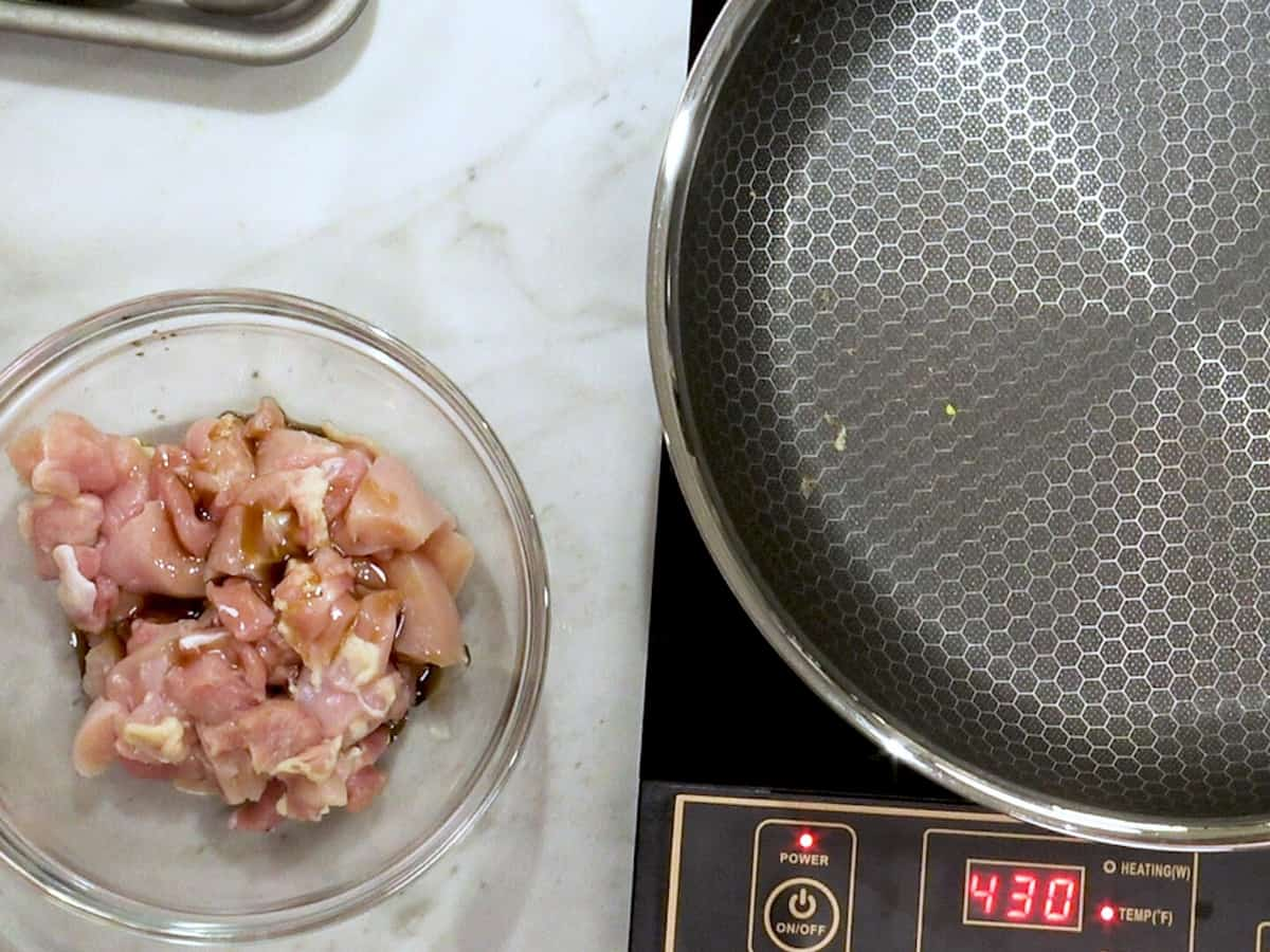 raw chicken in a bowl next to a pan on a small electric burner