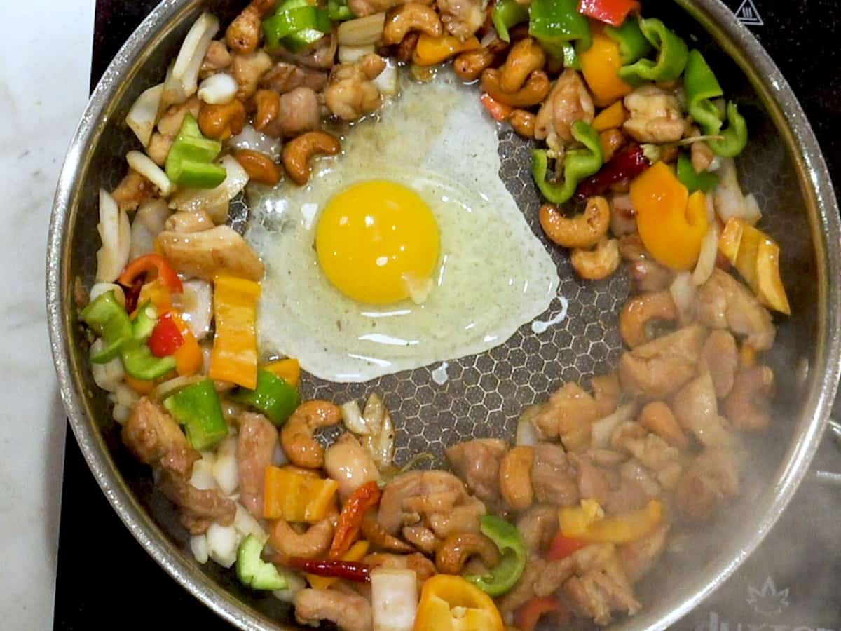 raw egg in a skillet with cooked chicken, vegetables, and cashews