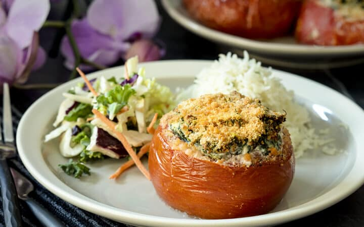 stuffed tomato on a plate with salad