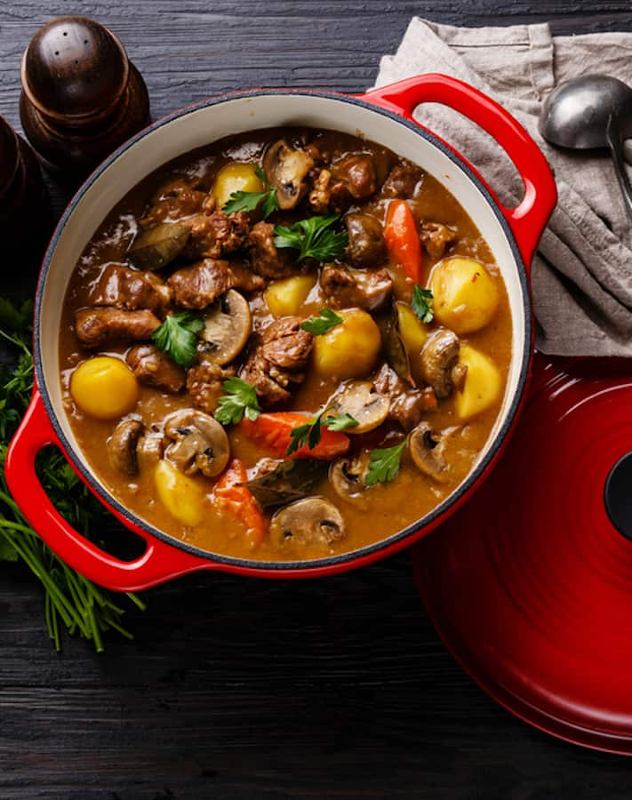 French Beef Stew in a vibrant red crock on a dark back drop. Background accents of a ladel, cilantro, and salt and pepper shakers.