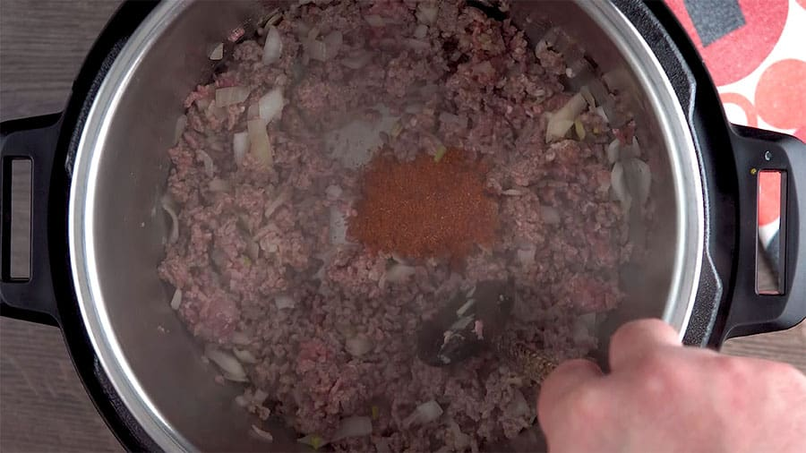Overhead shot of sauteing beef, onions and garlic with taco seasoning and salt.