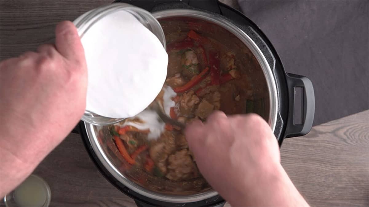 pouring coconut milk over a coked panang curry in an instant pot