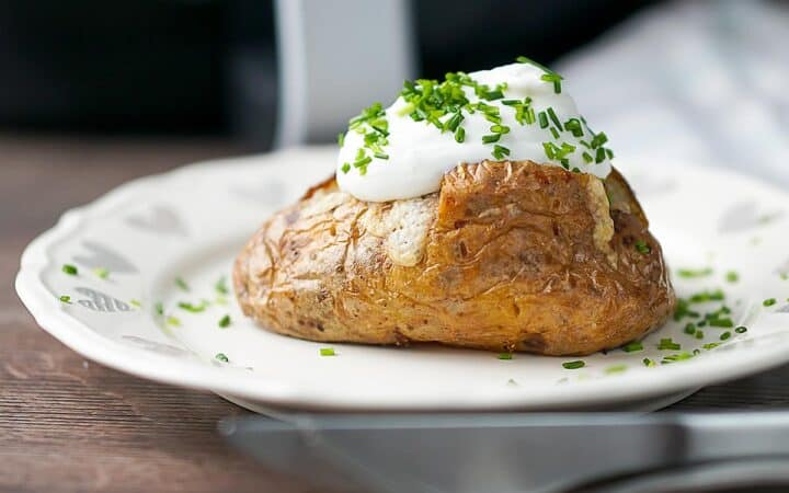 Side shot of a baked potato on a white plate