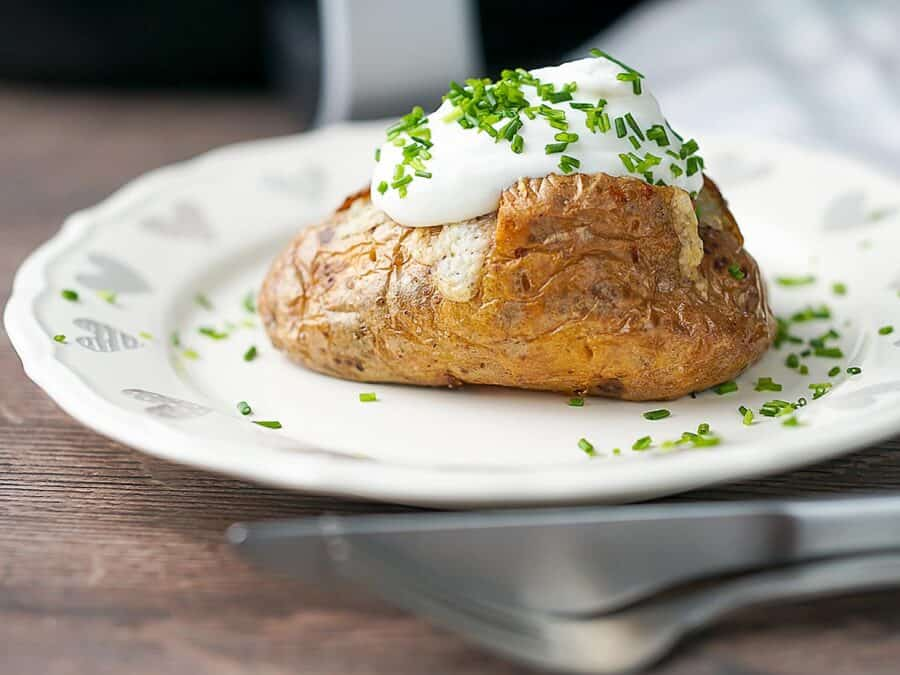 An air fryer jacket potato topped with sour cream