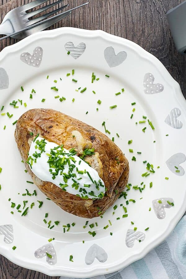 Overhead shot of a baked potato garnished with herbs