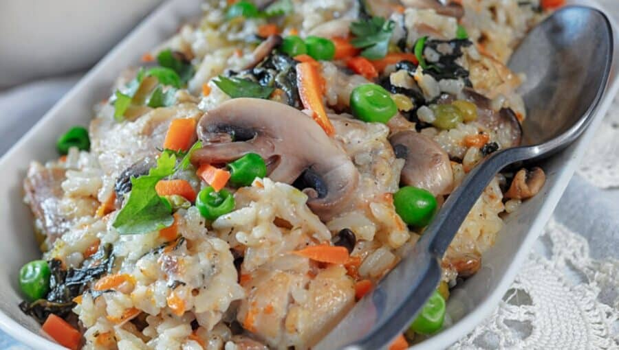 Creamy Chicken and Rice with mushrooms, peas, and carrots served on a white platter. A spoon is placed to the side for serving.