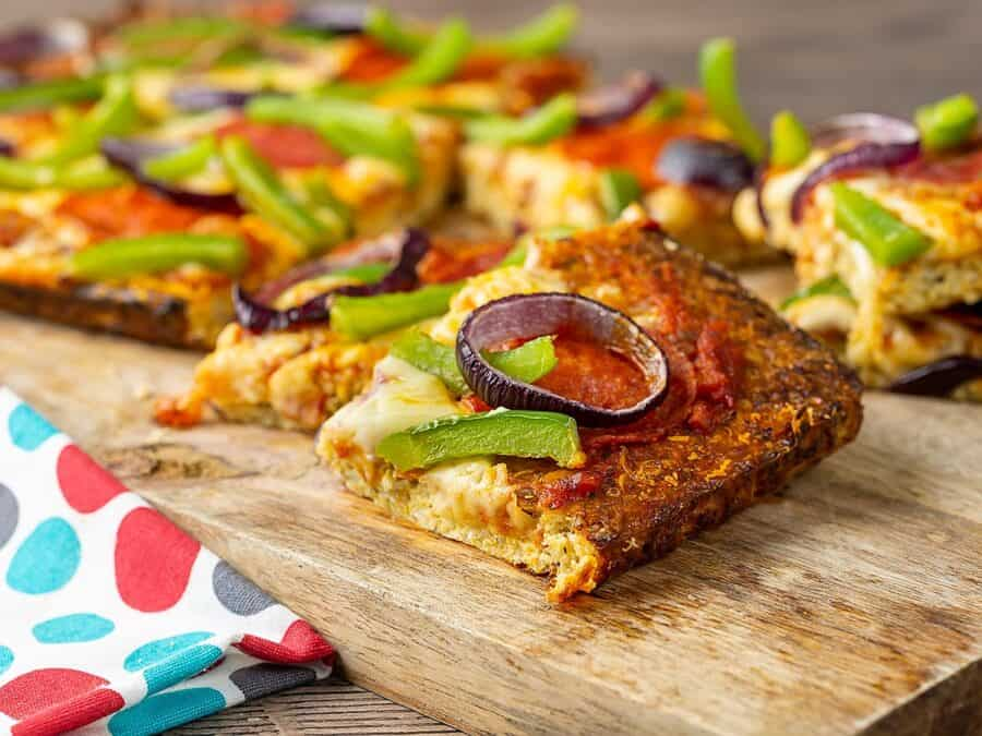 slices of low carb pizza on a cutting board. the pizza slices are topped with onions, peppers, cheese, and sausage.