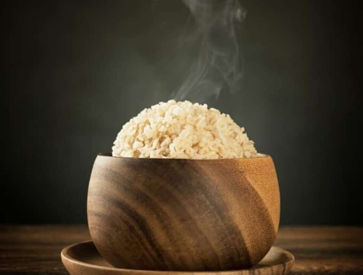 Brown rice served in a wooden bowl on a wooden saucer with steam rising from the top.